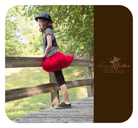 Girl in a red tutu looks thoughtfully over a bridge in North Little Rock