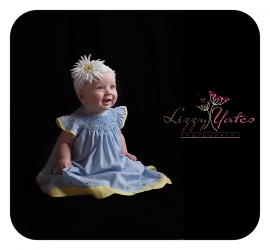 6 month old girl smiles in her blue dress during a West Little Rock family photography session