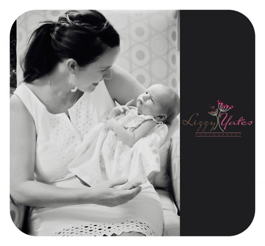 A mother smiles at her newborn daughter during their in home photography session in Little Rock