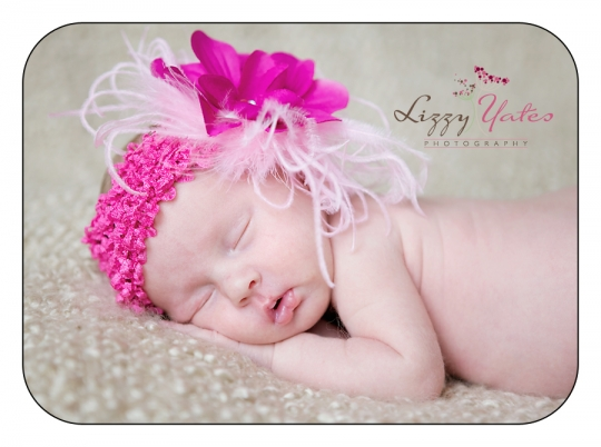 A newborn baby girl sleeping and wearing a pink headband during her pictures in Little Rock Arkansas